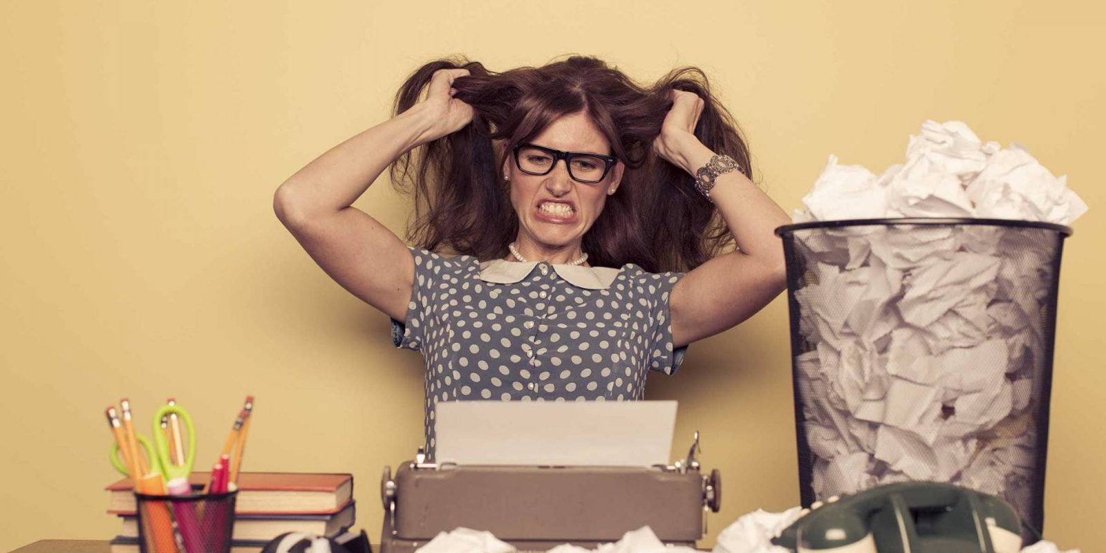 caucasian brunette woman looking frustrated and pulling her hair in front of a typewriter with a trashcan full of crumpled paper who needs to use our digital marketing services to make writing easier